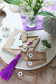 Hand-crafted Easter decorations in natural shades and purple on chopping board