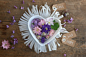 Flowers in heart-shaped bowl on fringed paper mat