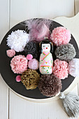 Geisha figurine and pompoms in pink and earthy tones on black plate