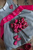 Rote Tannenbäumchen aus Filz mit Zahlen auf kariertem Kinderkleid