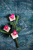 Gifts with numbered, red felt Christmas trees on fir twig