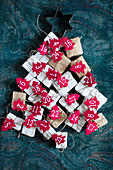 Gifts with numbered, red felt Christmas trees arranged in tree shape