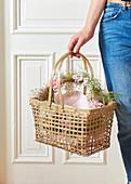 Hand hält Korb mit Kranz aus Blüten und Samenständen