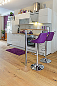 Purple bar stools at counter in kitchen area of open-plan interior