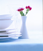 Stacked crockery and vase of carnations