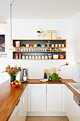 Kitchen counter with wooden worksurface below crockery on shelves