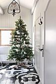 Schlicht geschmückter Weihnachtsbaum auf bemaltem Boden
