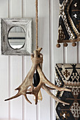 Lamp made from antlers and rope in front of white wall cladding
