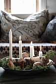 Advent arrangement of four candles on piece of birch bark in dish
