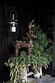 Bark reindeer figure and fir branches next to front door
