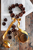 Circle of pine cones and gold ribbon on book pages