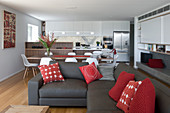 Sofa set with red scatter cushions in elegant, open-plan interior