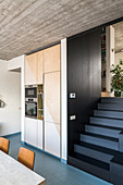 Fitted kitchen appliances next to steps with dark wood cladding leading to raised level