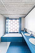 Light blue tiles and concrete ceiling in bright bathroom