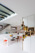 White dining table and colourful chairs in open-plan kitchen