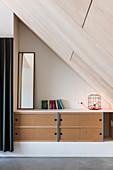 Sideboard with sliding doors below sloping ceiling clad in plywood
