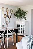Dark dining table with white chairs and display cabinet, old tennis rackets as wall decoration
