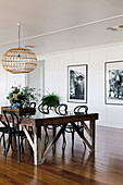 Rustic dining table with chairs in an open living room, black and white photos on the wall