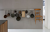 Collection of kitchen utensils and delicate wooden chair hung on grey wall