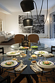 Set glass table below direct lighting in open-plan interior with black-and-white photos on white wall