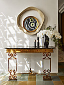 Antique console with marble top and orchid flowers, mirror above
