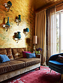 Consoles with turquoise vases on gold-colored wallpaper above an upholstered sofa