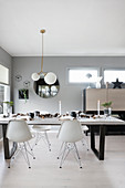 Festively decorated dining table and classic chairs in bright, open-plan interior