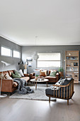 Leather sofas and armchair in cosy living room with grey walls