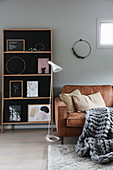 Scatter cushions and giant knit blanket on leather sofa, standard lamp and shelves
