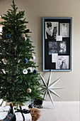 Christmas tree next to collage of photos on wall