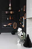 Ornaments on black wall and magnetic pin board in corner of kitchen