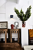 Console tables with works of art, light on white wall above