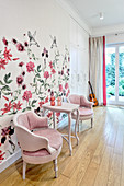 Pink armchairs against wall with floral wallpaper