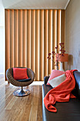 Designer armchair and leather sofa in living room with slatted wooden partition in background