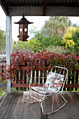Vintage rocking chair with seat cushion on wooden veranda