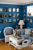 Gallery of black-and-white photos on blue wall, sofa and wicker furniture in living room