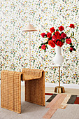 Rattan table, floor lamp and side table with a bouquet of red roses in front of floral wallpaper