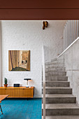 Retro sideboard against brick wall next to concrete staircase