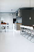 Row of folding chairs on white floor in front of open-plan kitchen