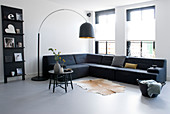 Arc lamp above sofa in minimalist living room in shades of grey