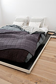 Deep, futon-style bed with layers of covers and quilted bedspread
