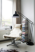 Designer armchair with sheepskin rug next to large anglepoise lamp and stacked books