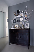 Black cabinet below gallery of pictures on grey wall in hallway