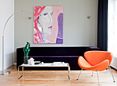 Orange designer armchair in front of purple velvet sofa in living room