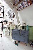 Grey chest of drawers below book racks on sloping walls
