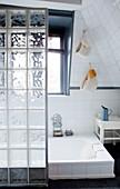 Glass-brick partition screening sunken bathtub
