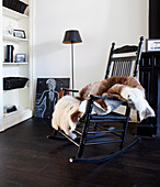 Black lacquered rocking chair with animal fur in front of a shelf