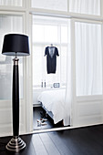 Black floor lamp in front of a glass room divider, with a view into the bedroom