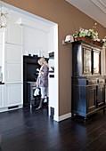 Antike Anrichte mit Blumenkorb vor hellbrauner Wand neben Durchgang, im Hintergrund Frau in der Küche