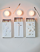 Matchboxes decorated in white, tealights and used matches